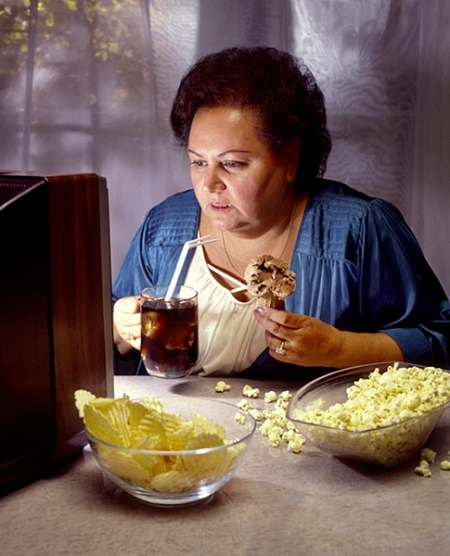 heavy woman watching TV while eating junk food
